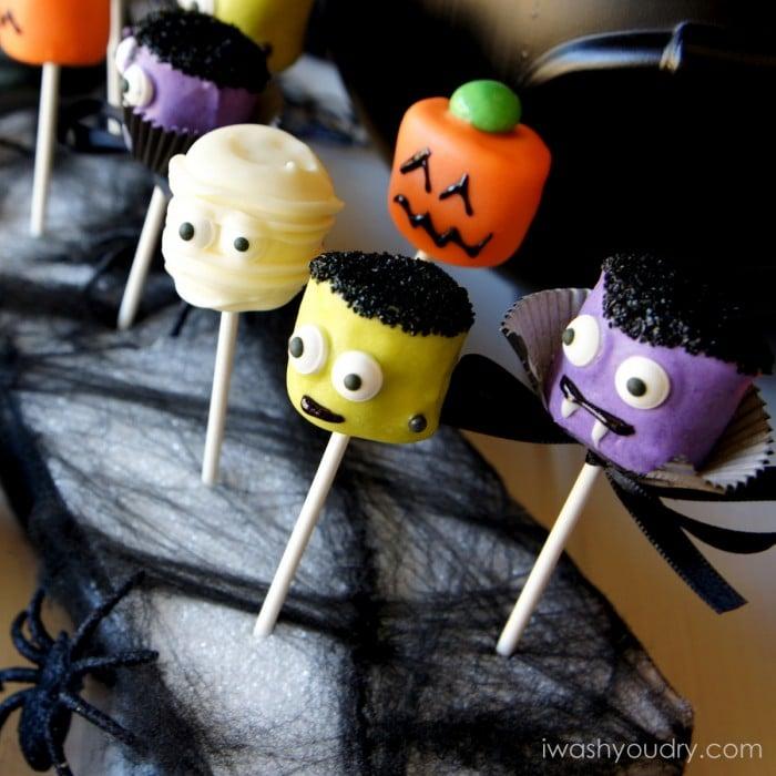 A Halloween themed display of Halloween themed Marshmallow pops - a mummy, a pumpkin, Frankenstein and a vampire