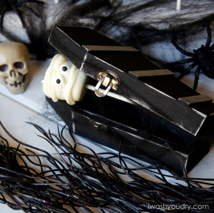 A display of a Mummy themed marshmallow pop in a closing coffin surrounded by other Halloween decorations