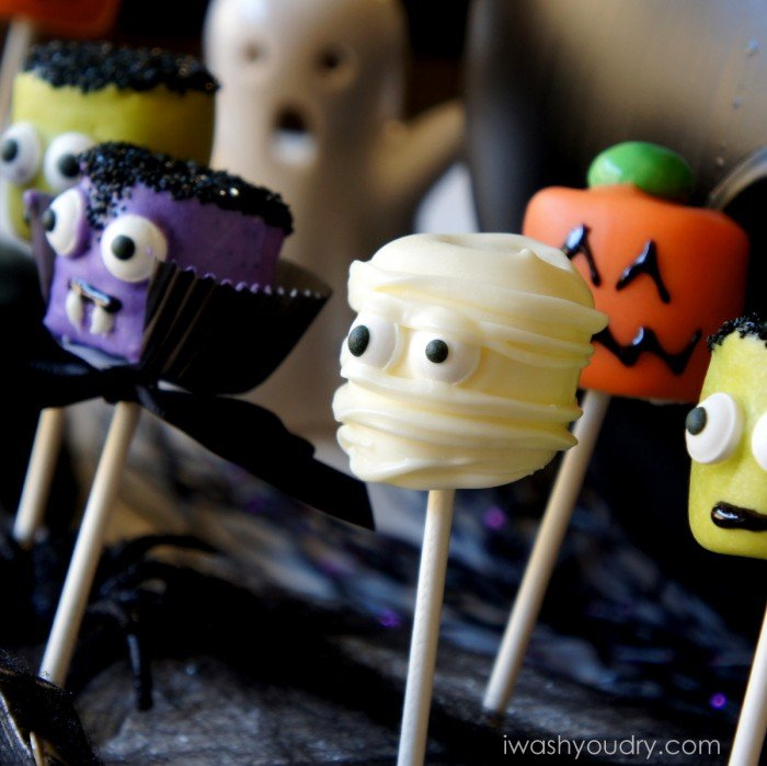 A close up view of Halloween themed Marshmallow pops - a mummy, a pumpkin, Frankenstein and a vampire