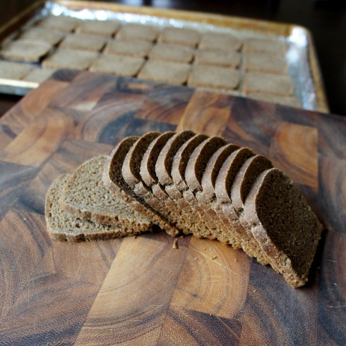 A sliced loaf of Cocktail Pumpernickel Bread on a a cutting board