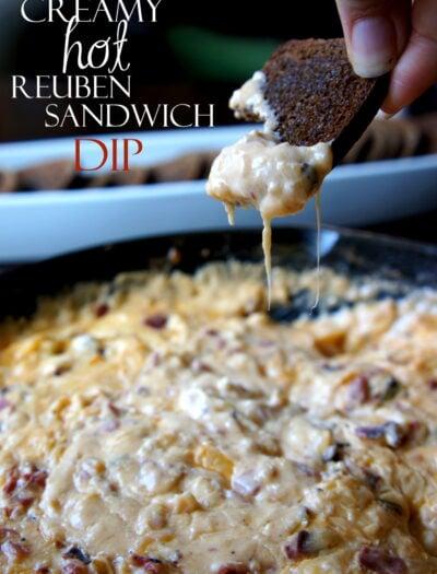 "A hand dipping a chip into a dip titled, ""Creamy Hot Reuben Sandwich Dip"""