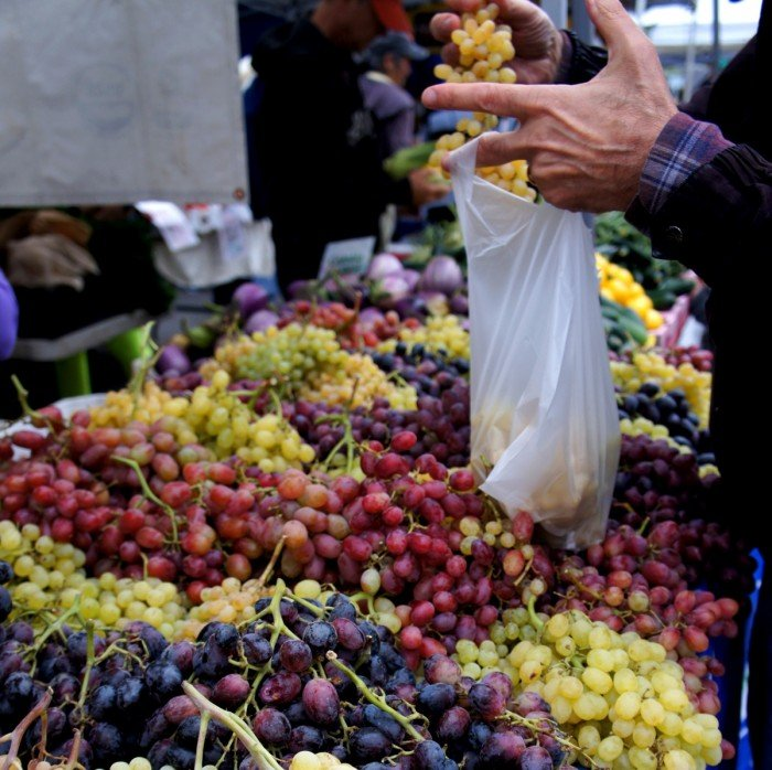 A large table of grapes and a man putting grapes in a plastic bag