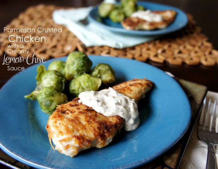 Cooked chicken breast on a blue plate topped with a white sauce and side of Brussels sprouts