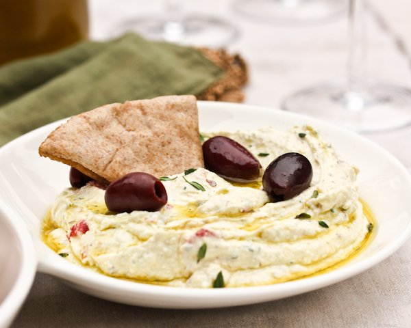 A triangle of pita bread dipped into a small bowl of his Spicy Feta Dip with Roasted Red Peppers