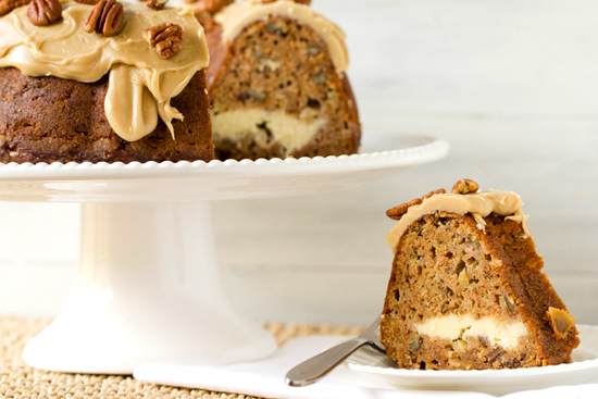 A slice of apple cream cheese bundt cake on a plate on a table next to a cake plate with the full cake