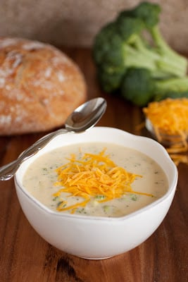 A bowl of white cream base soup topped with orange shredded cheese