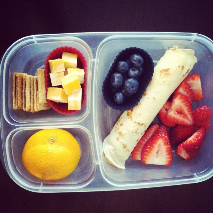 A plastic container filled with food, with easy bento lunch ideas - Cheese, crackers, fruit and a rolled tortilla