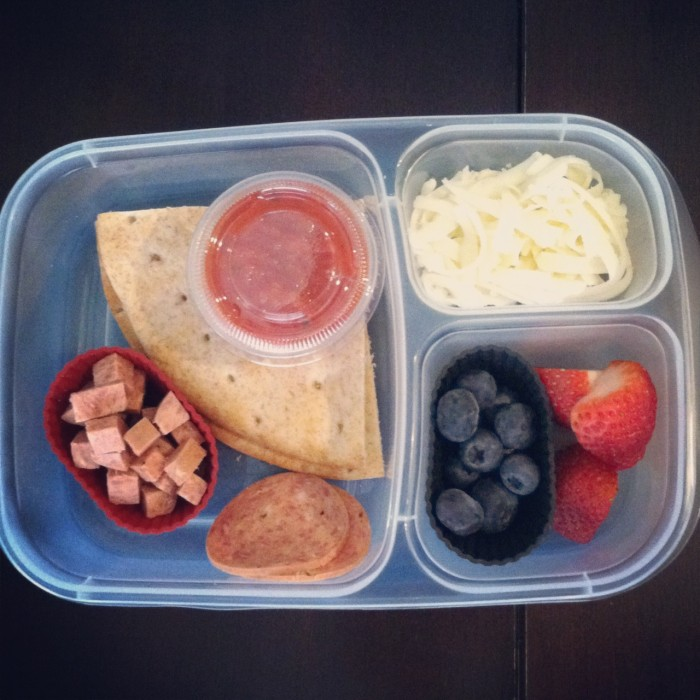 A plastic bento container filled with homemade lunch pizza makings and berries