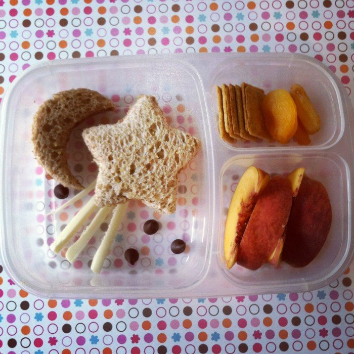 A Bento styled plastic container with dividers showcasing an easy lunch of a star shaped sandwich shaped to look like a shooting star, crackers and peach slice