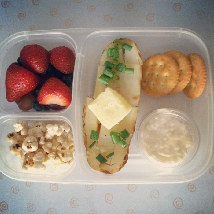 A bento box filled with strawberries, popcorn, half a baked potato with butter on top, chips and dip
