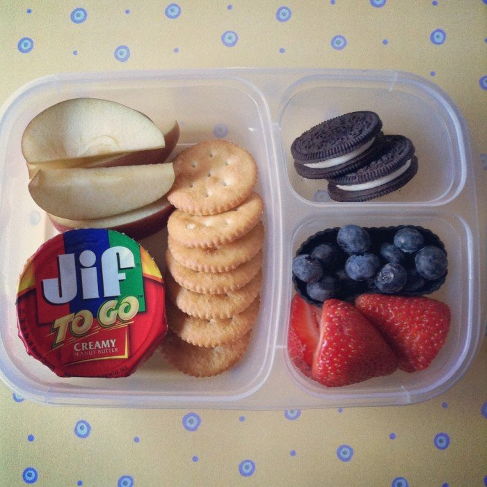A Bento styled plastic container with dividers showcasing an easy lunch of crackers, peanut butter, apples, cookies and fruit