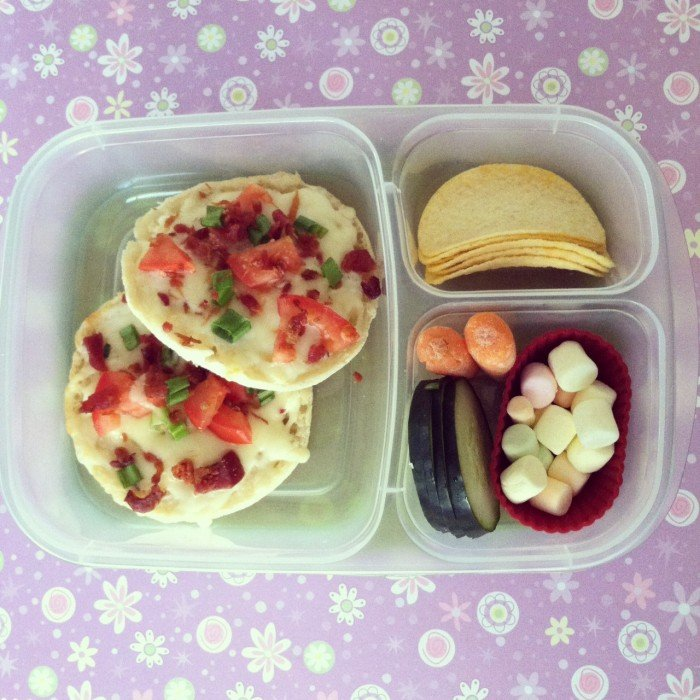 A plastic bento container filled with different types of foods for lunch