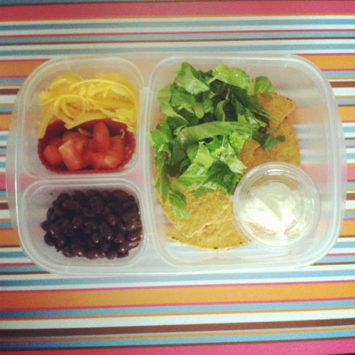 A close up of a bento styled plastic container with an easy lunch example