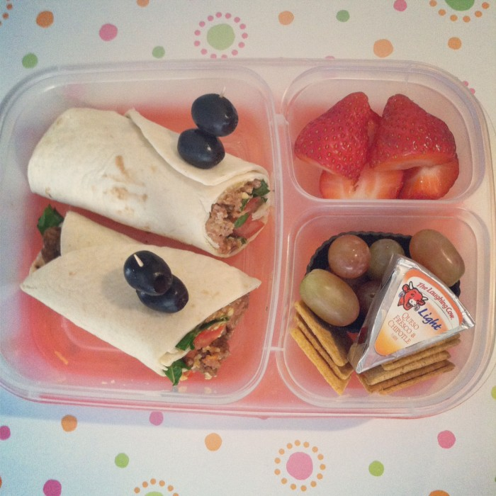 A bento box filled with two halves of a wrap, berries, grapes, crackers and a cheese wedge in the compartments