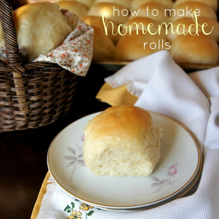 A plate with a roll on it in front of a pan of rolls
