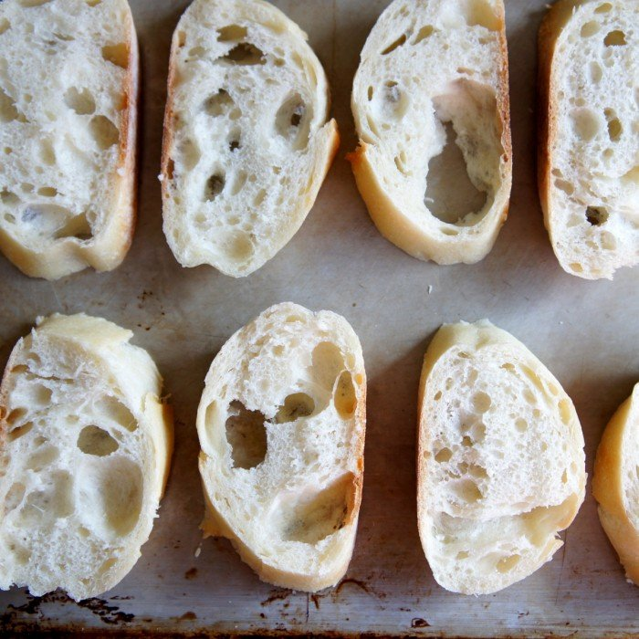 A close up of baguette slices on a pan