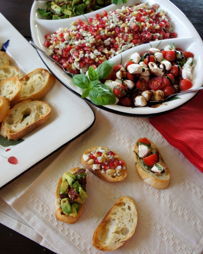 Three crostini\'s next to a tray of topping options and a plate of baked baguette slices