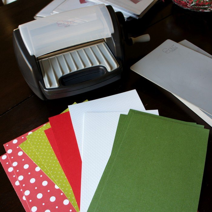 An Epic Six Cutting and Embossing Tool next to a pile of Christmas colored paper