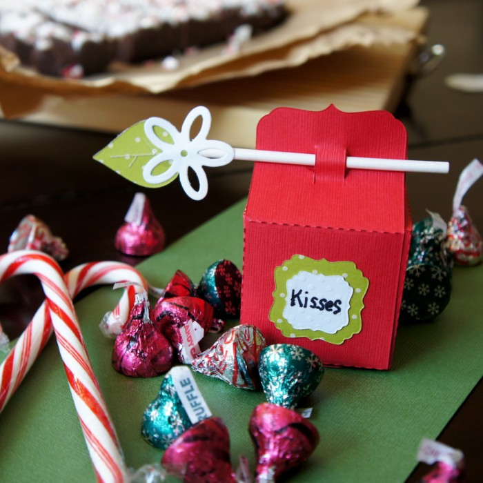 Close up of a baker box next to a pile of holiday colored Hershey kisses and peppermint candy canes