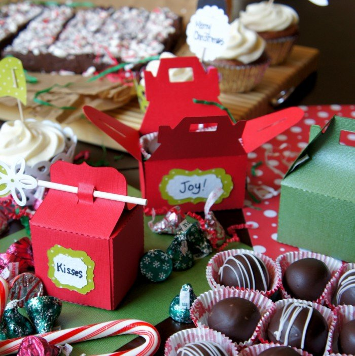Decorated dessert boxes surrounded by chocolate holiday treats