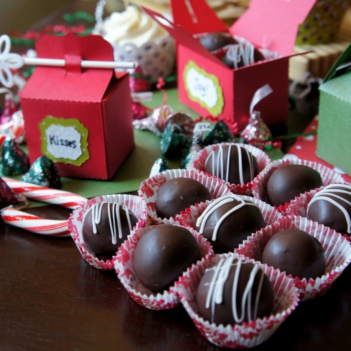 A close up of chocolate truffles on a table next to small gift boxes