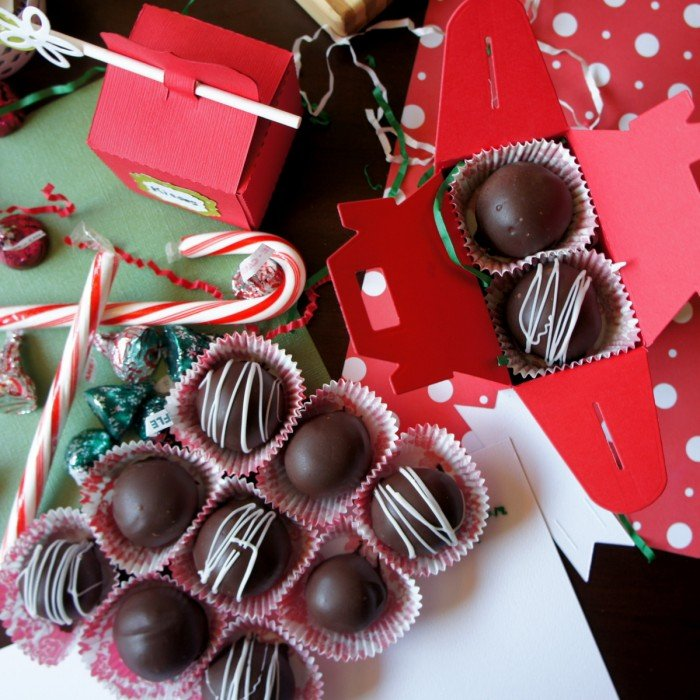 A close up of chocolate dipped treats next to an open baker box showing it\'s contents