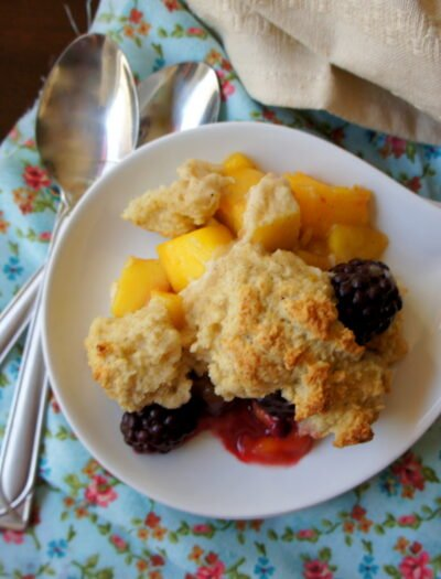 A plate with a scoop of cobbler on it with mango and blackberry