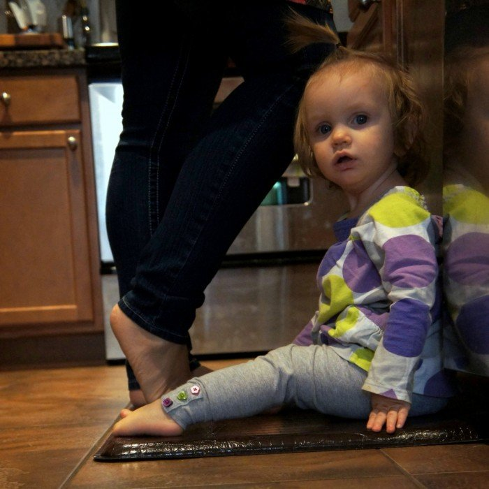 A little girl sitting on the floor in the kitchen