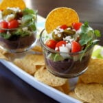 Five Layer Black Bean Dip in a glass cup over a tray of chips