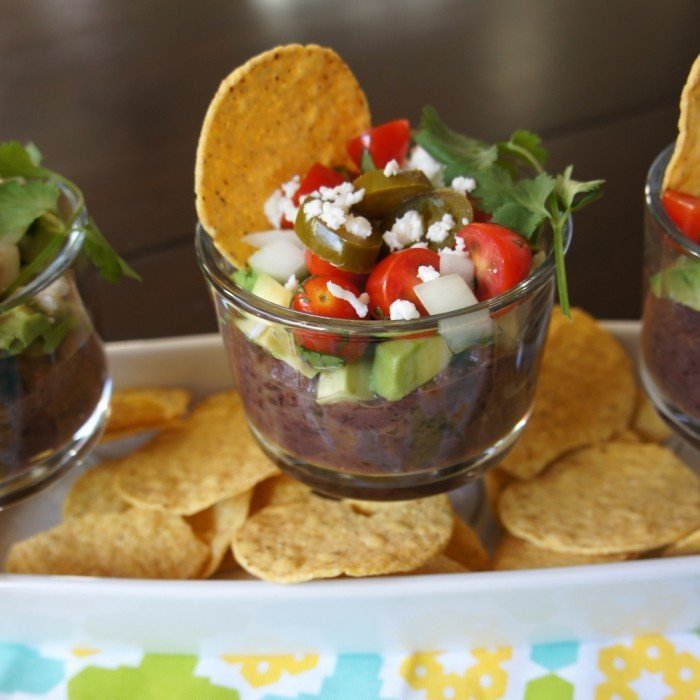 Bean dip in a small glass bowl with a chip surrounded by a pile of chips