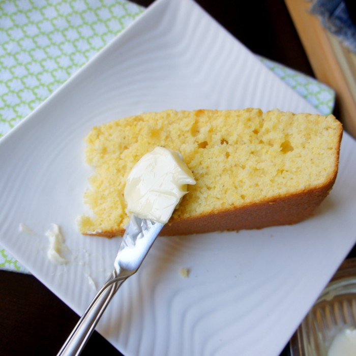 A piece of cornbread on a plate being spread with butter