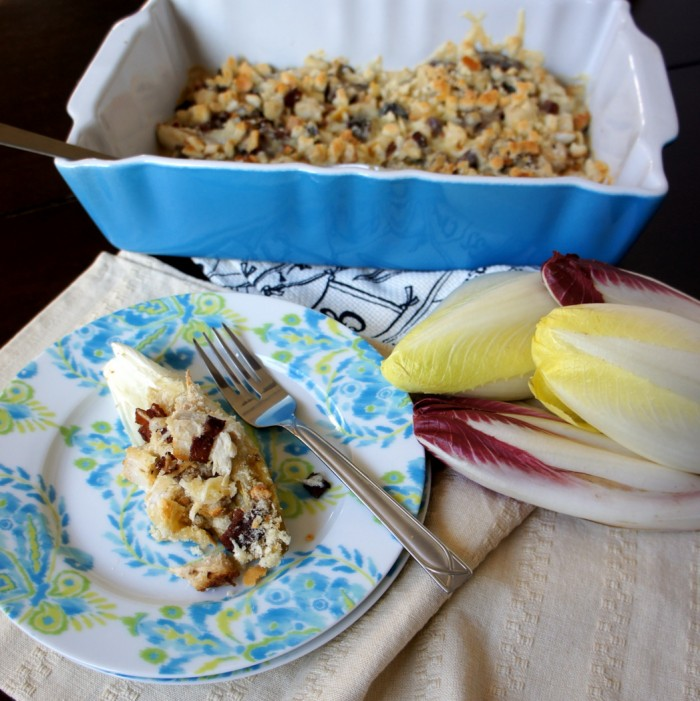 A plate with a Turkey and Bacon Stuffed Endive in front of a pan of stuffing