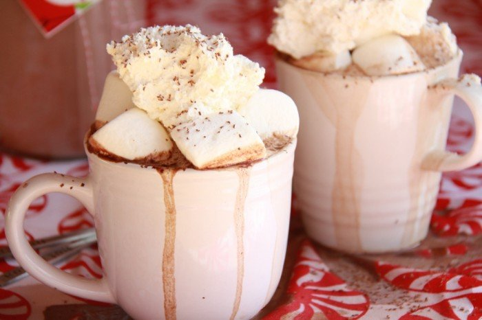 Two mugs of over flowing hot chocolate topped with large marshmallow sand whipped cream
