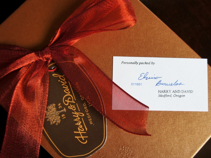 A close up of the top of a golden Harry & David box tied with a bow and a quality card of who packed it