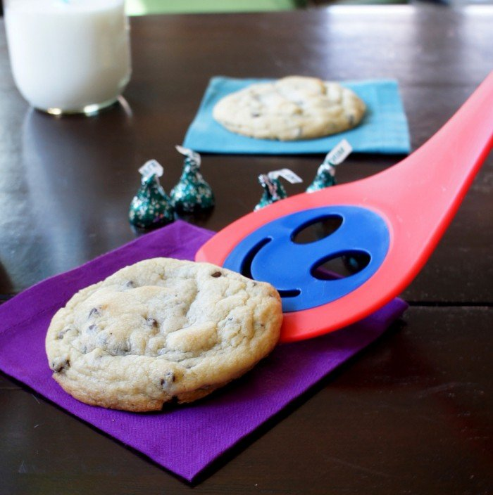 A cookie being place on a napkin with a smiley faced spatula