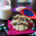 Mint Truffle Stuffed Chocolate Chip Cookies stacked on top of each other on a napkin next to a glass of milk