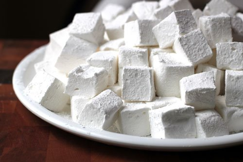A close up of a large pile of square homemade marshmallows