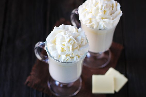 Two glasses of homemade white hot chocolate topped with whipped cream