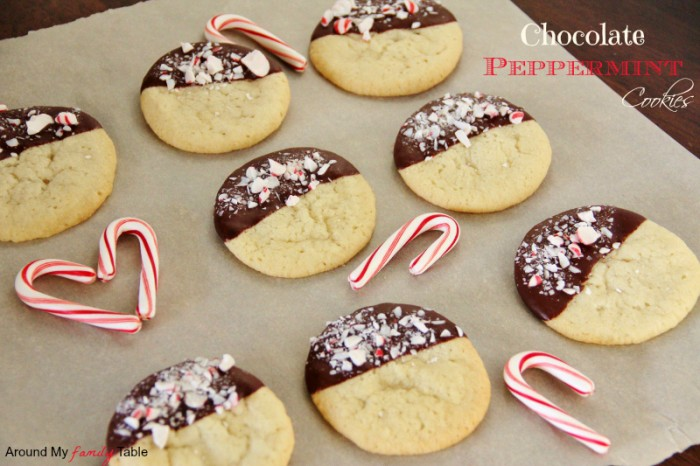 A pan of sugar cookies half dipped in chocolate and crushed peppermint
