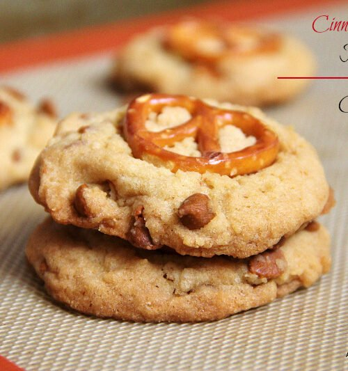 A close up of two cookies on top of each other with cinnamon chips and a pretzel on top
