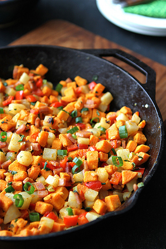 A close up of a pan of sweet potato hash with Canadian Bacon and vegetables
