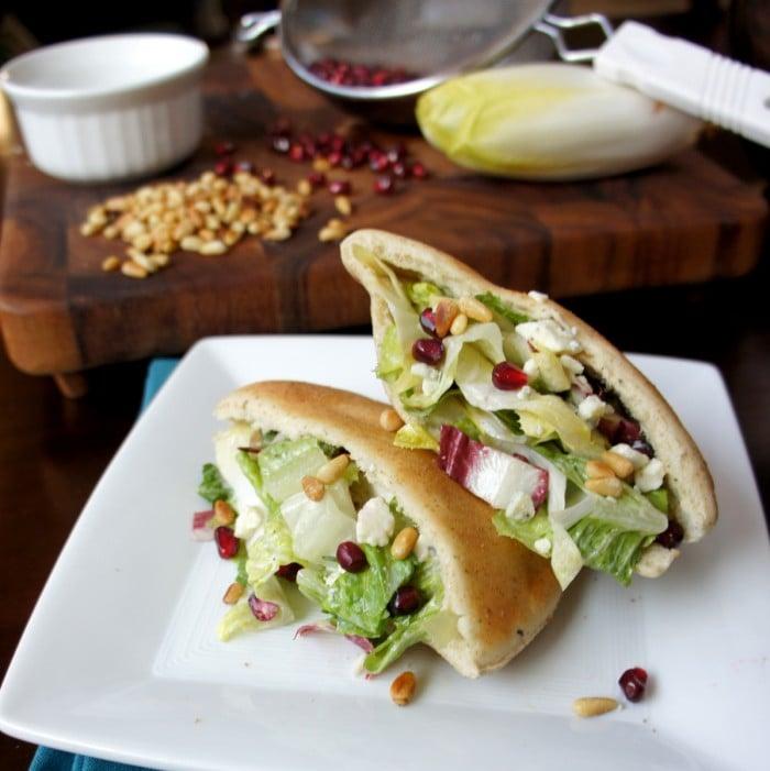 Two halves of a pita pocket sandwich on a plate