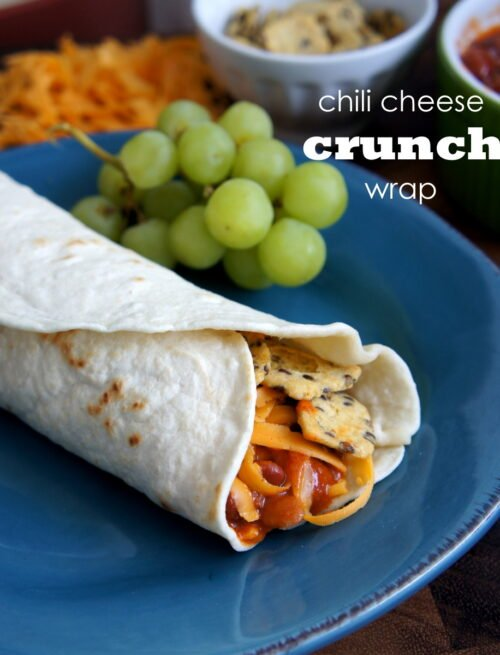 A blue plate with a Chili Cheese Crunch Wrap on it with a side of grapes
