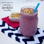 A smoothie in a glass cup with granola on top and a blue straw next to a small bowl of granola