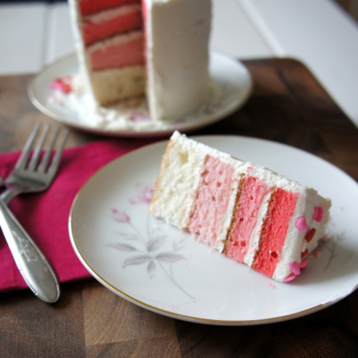 A slice of four layer cake on a plate next to the full cake it was removed from