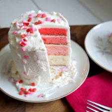 A 4 layer ombre cake with white frosting on a plate and a slice removed from it