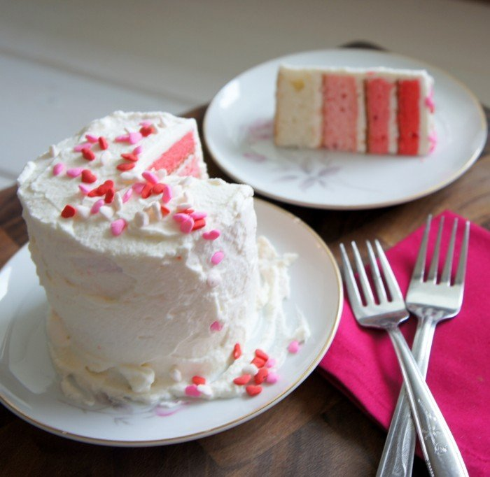 A white cake on a plate with a slice removed and next to it a second plate with the removed slice.