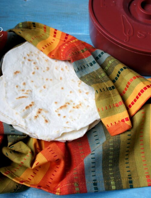 A pile of homemade tortillas in a colorful cloth next to a tortilla warmer