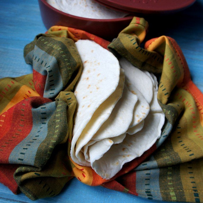A pile of folded homemade tortillas in a colorful cloth next to a tortilla warmer