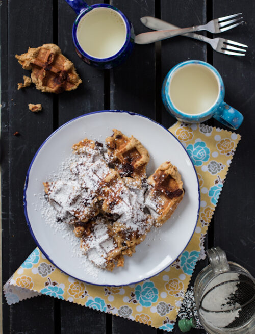 A plate of waffle cookies on a table next to a mug of milk
